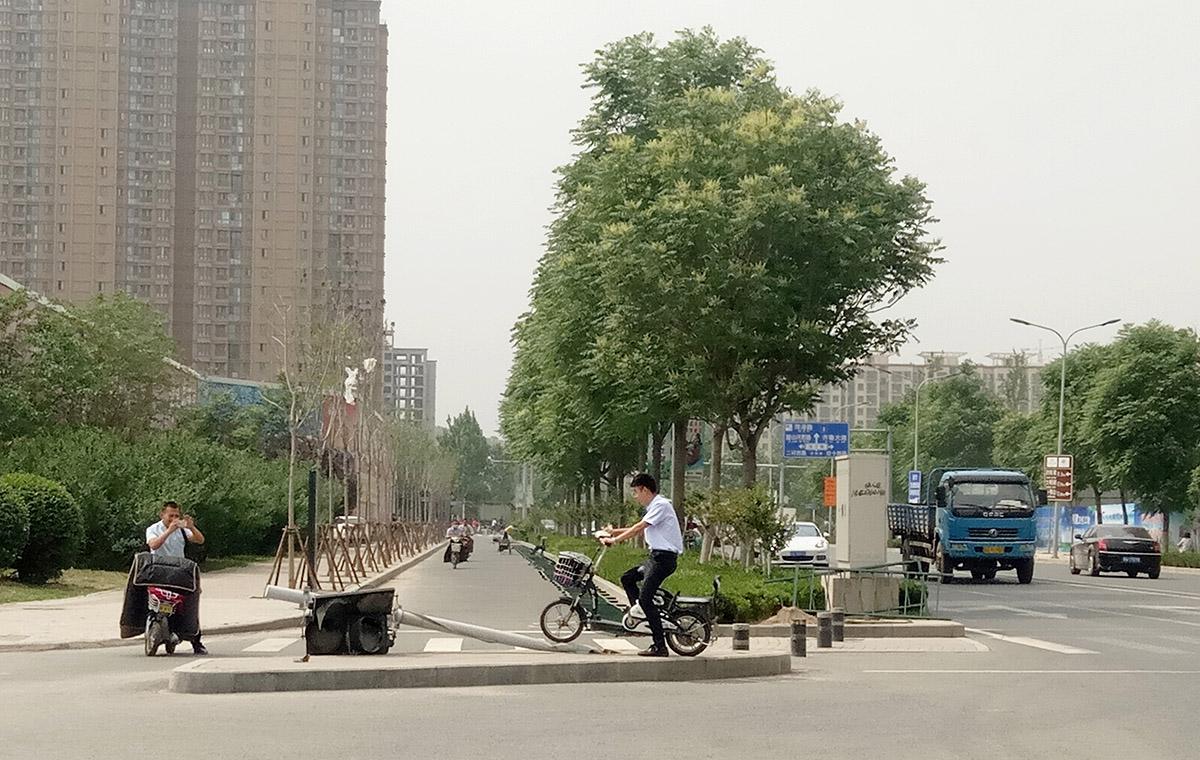 """躺着""""干活""""?济南齐州路一交通信号灯歪倒引路人合影"""