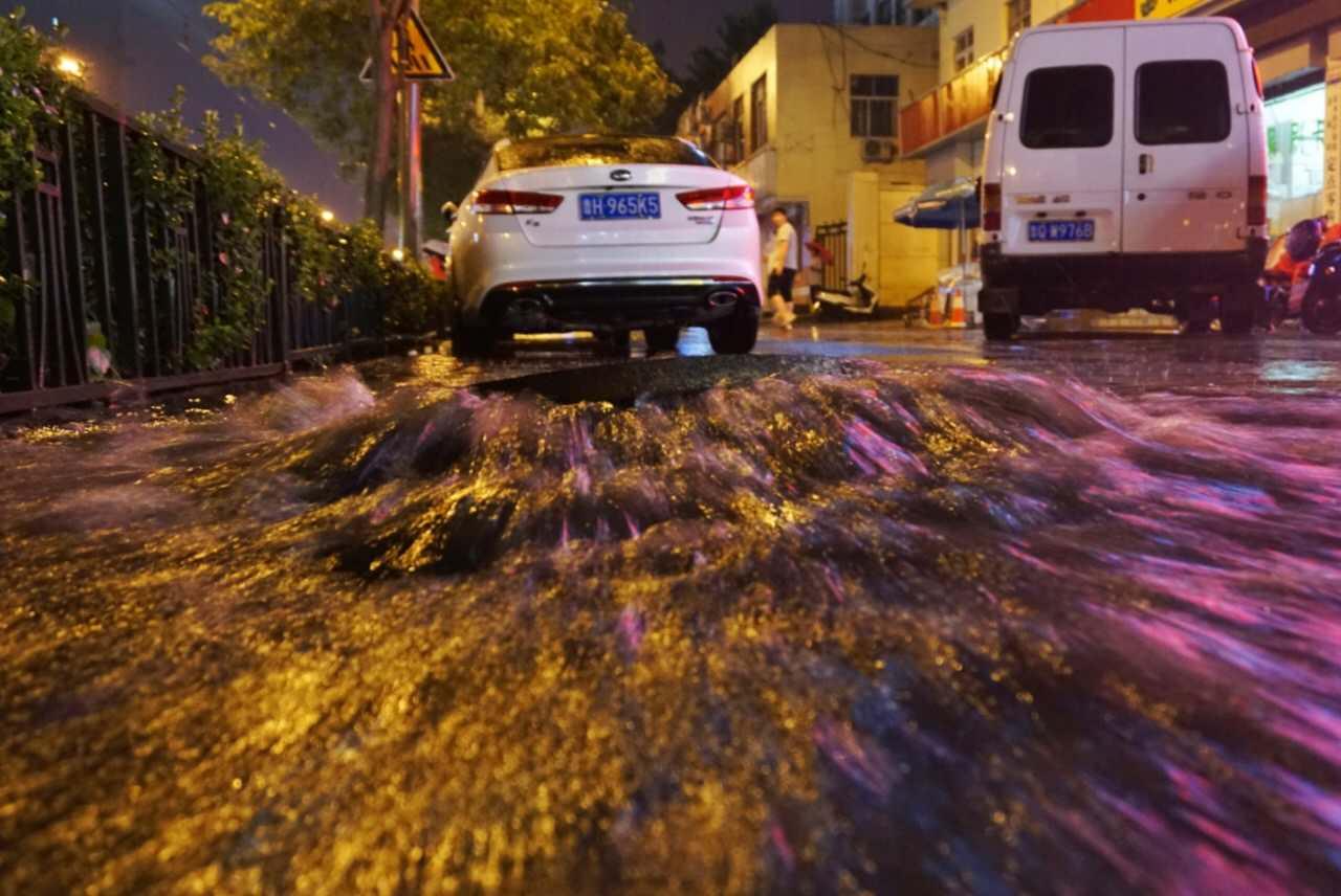 实拍大雨突袭济南:路面成河道 井盖变喷泉