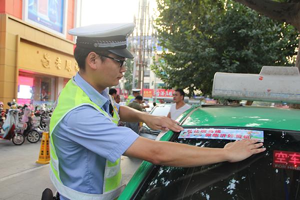费县交警开展礼让斑马线倡导活动 为出租车发放宣传车贴