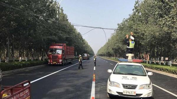 34秒丨暖心!电缆被刮断挡路 潍坊民警托举1小时让车辆通行