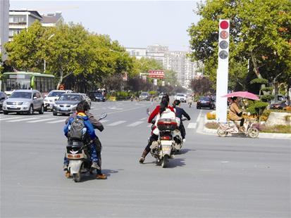 邹城一摩托车主单手骑车闯红灯 撞上轿车前空翻180度解体
