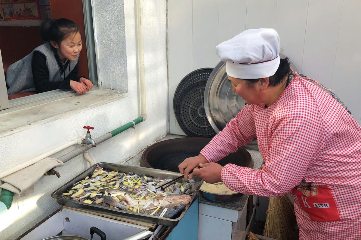 """7.家家户户都炸""""花鱼"""",寓意年年有余。一个小孩正在看奶奶炸""""花鱼"""".jpg"""