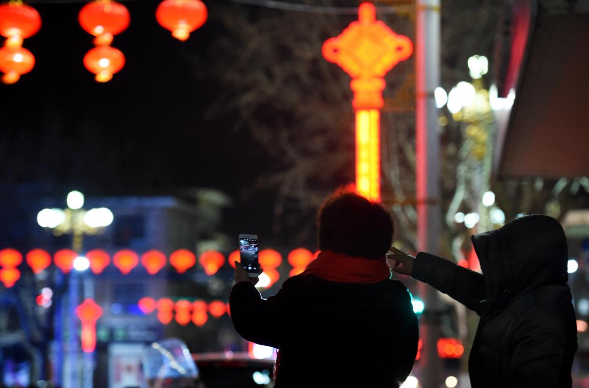 4.岛上挂满了红灯笼,两名海岛居民对着红灯笼拍照,海岛上年味渐浓.jpg