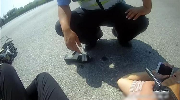 骑电动车大妈正中午被撞倒地 平原民警垫衣服撑伞守护