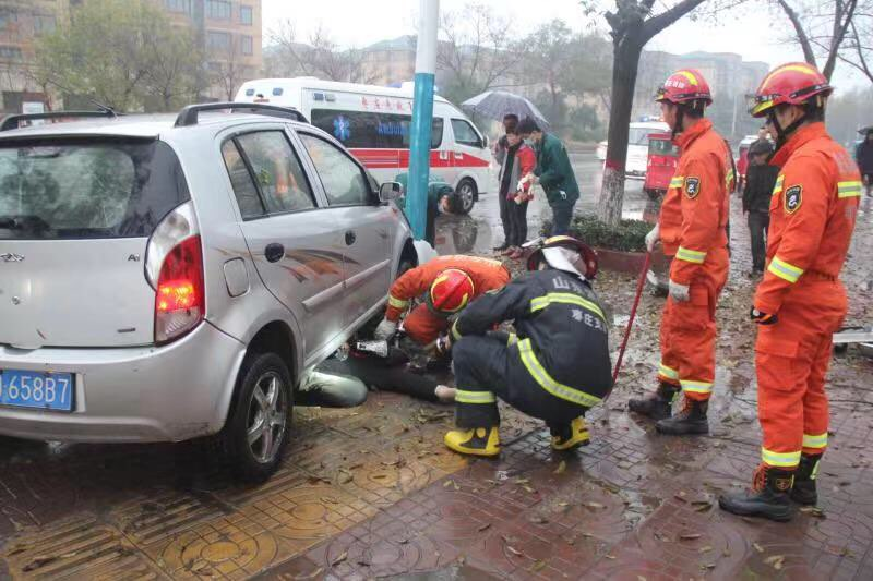 女子骑车卷入车底 消防员和群众合力抬车救人