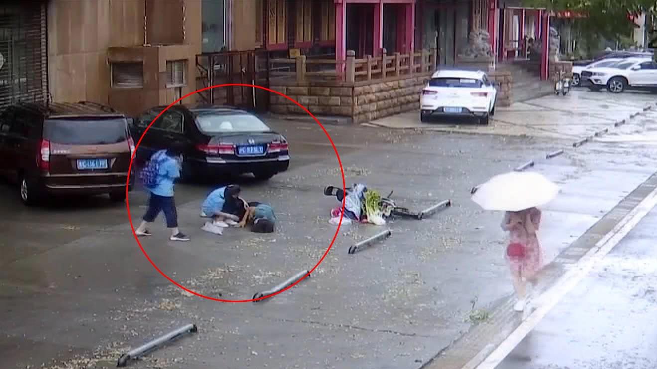 69秒丨淄博老人骑车摔倒 两名学生雨中为其撑伞施救