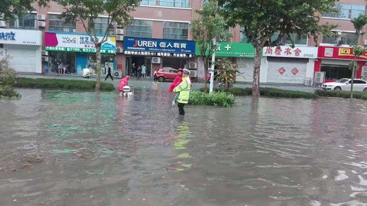 33秒丨暖!路面积水严重,临清这名交警将娃一个个抱过马路