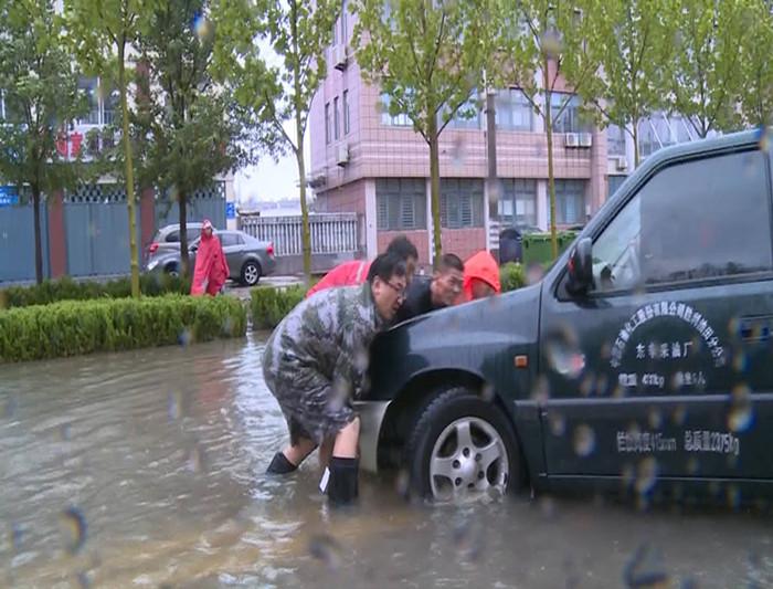 48秒丨暖新闻!道路积水东营街道一车辆陷井口 众人合力推车