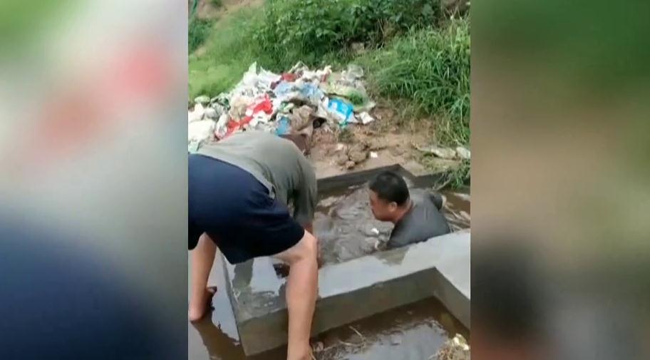 65秒丨暴雨过后他跳入一人深的排水沟中 徒手清理垃圾一个多小时