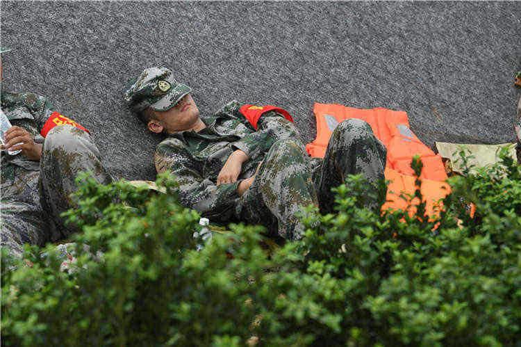 组图|烈日为被红砖作床 救援官兵顶着烈日背靠大棚休整
