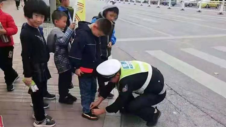 79秒丨又帅又可爱!红绿灯下,五莲辅警为一年级小朋友系鞋带