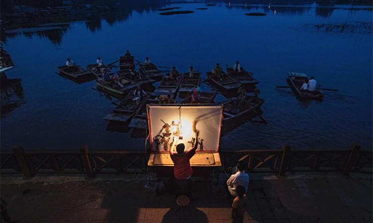 夜色朦胧 非遗传人微山湖表演水上皮影戏