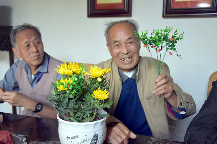 社区老人在展示制作的茱萸花卉。IC 资料图