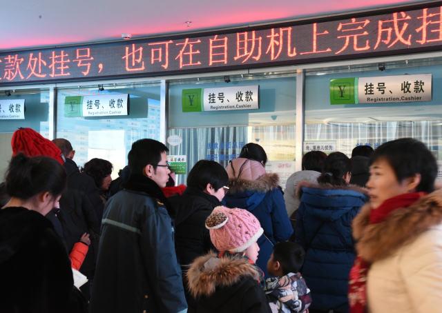 1月10日,在哈尔滨市儿童医院排队挂号交款的市民.