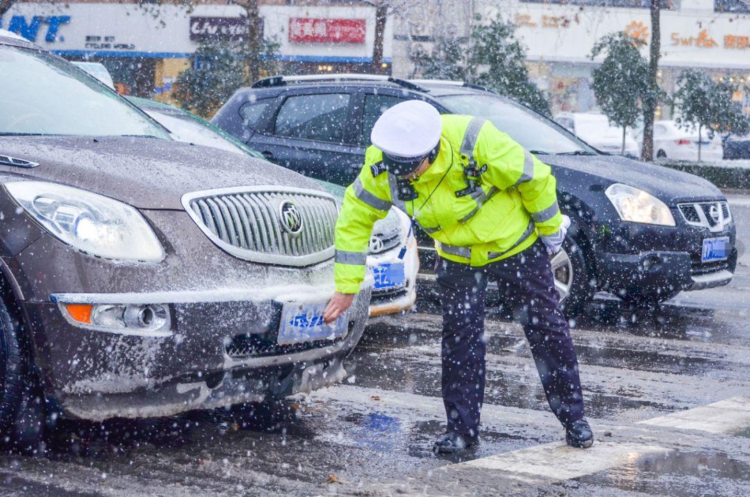 车辆等红灯时,擦去车牌上积雪