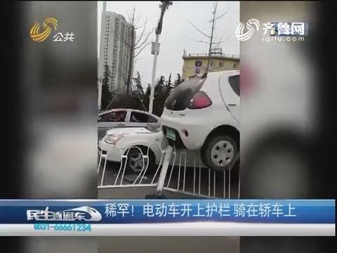 临沂:稀罕!电动车开上护栏 骑在轿车上