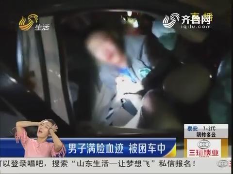 烟台:男子满脸血迹 被困车中