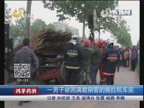 淄博:一男子被困满载钢管的拖拉机车底