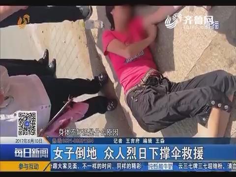 青岛:女子倒地 众人烈日下撑伞救援