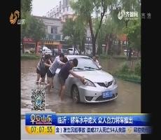 临沂:轿车水中熄火 众人合力将车推出