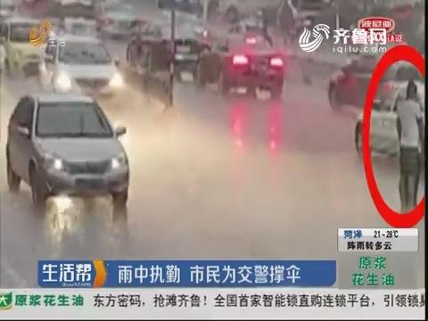 淄博:雨中执勤 市民为交警撑伞