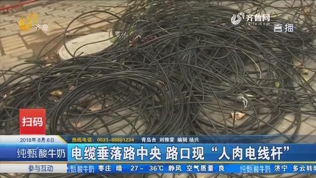"""青岛:电缆垂落路中央 路口现""""人肉电线杆"""""""
