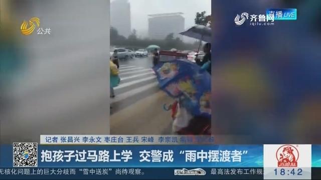 """枣庄:抱孩子过马路上学  交警成""""雨中摆渡者"""""""