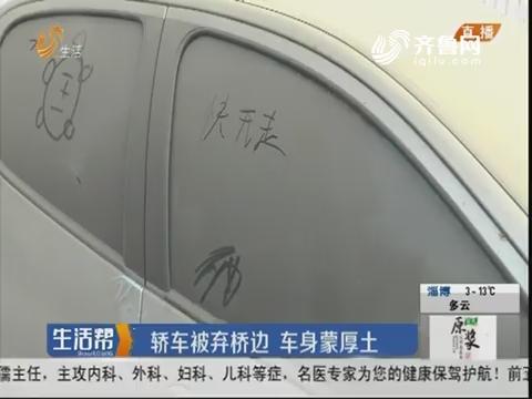 济南:轿车被弃桥边 车身蒙厚土