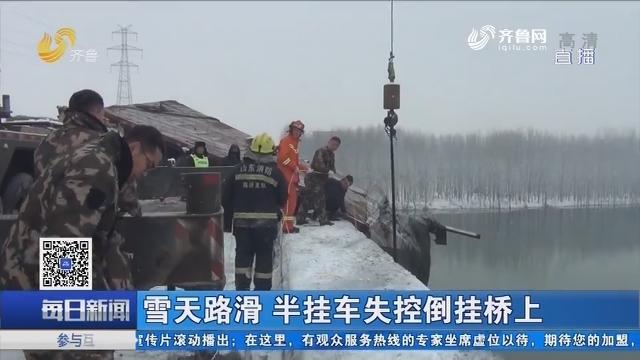 临沂:雪天路滑 半挂车失控倒挂桥上
