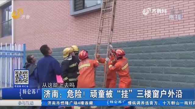 """济南:危险!顽童被""""挂""""三楼窗户外沿"""