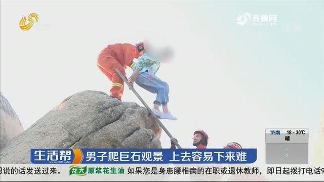 济宁:男子爬巨石景观 上去容易下来难