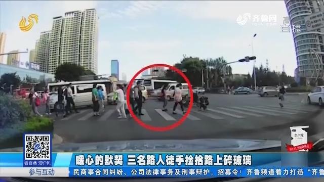 青岛:暖心的默契 三名路人徒手捡拾路上碎玻璃