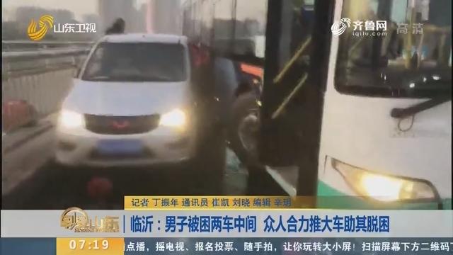 【闪电新闻排行榜】临沂:男子被困两车中间 众人合力推大车助其脱困