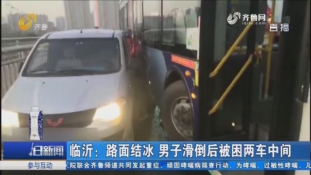 临沂:路面结冰 男子滑倒后被困两车中间
