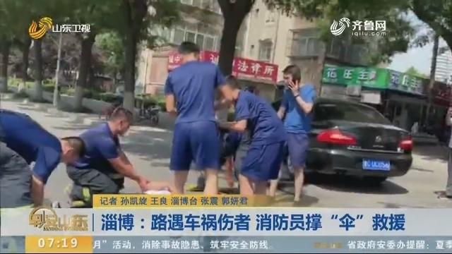 """淄博:路遇车祸伤者 消防员撑""""伞""""救援"""