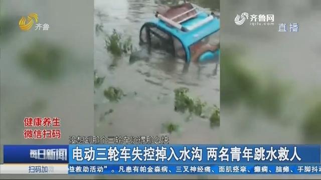 青岛:电动三轮车失控掉入水沟 两名青年跳水救人