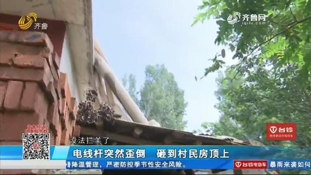 济南:电线杆突然歪倒 砸到村民房顶上
