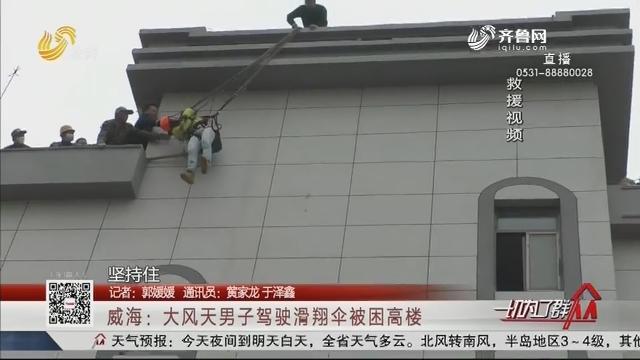 威海:大风天男子驾驶滑翔伞被困高楼