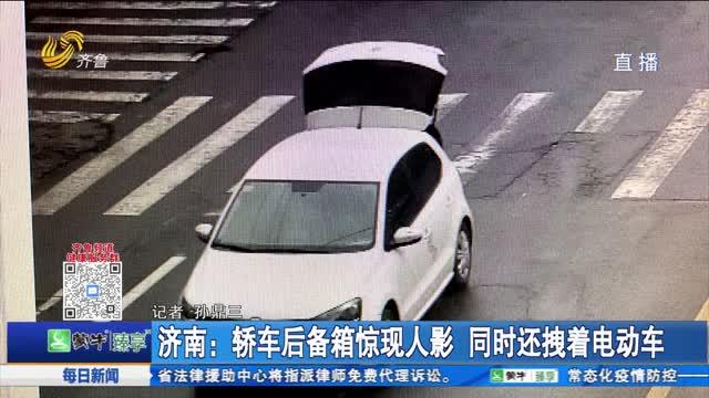 济南:轿车后备箱惊现人影 同时还拽着电动车
