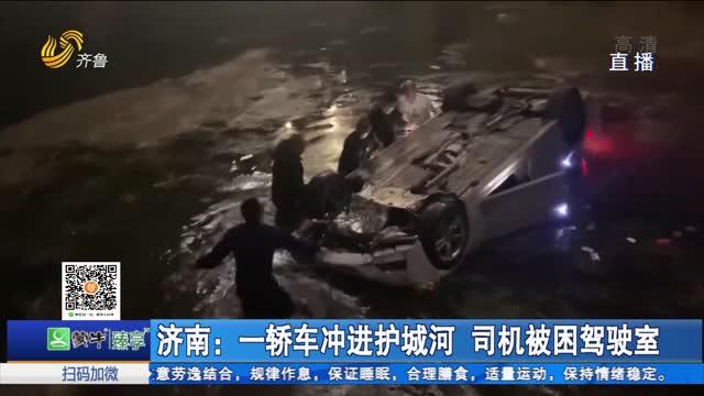 济南:一轿车冲进护城河 司机被困驾驶室