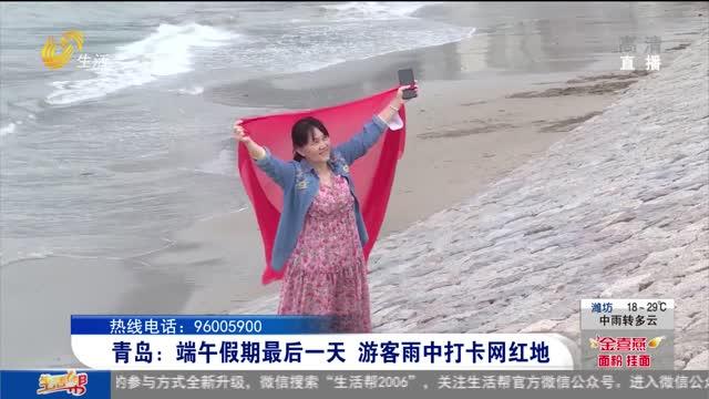 青岛:端午假期最后一天 游客雨中打卡网红地
