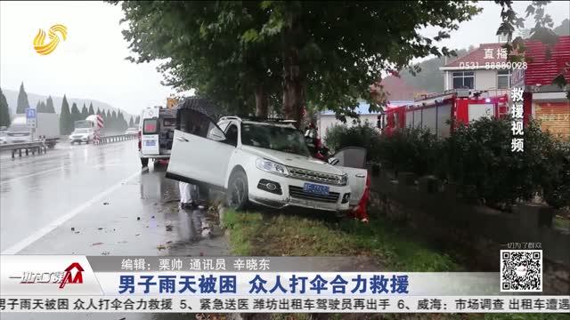男子雨天被困众人打伞合力救援